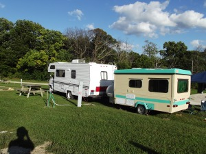 Class C Motorhome with a small trailer in back with beds for children.